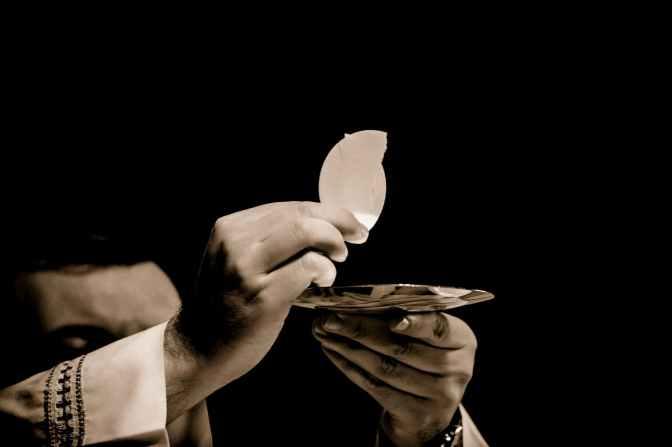 priest holding hostia
